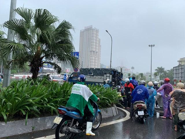 Người dân chạy xe máy xếp hàng lần lượt đợi xe tải vận chuyển qua cầu Bãi Cháy