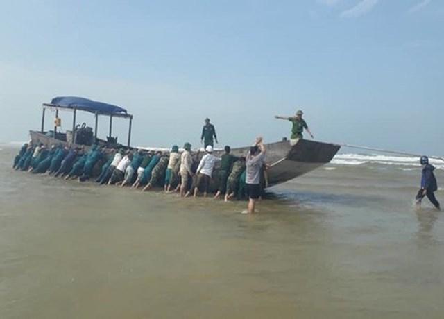 Lực lượng chức năng cùng người dân địa phương đang lai dắt chiếc tàu vào bờ. Ảnh CQCN.