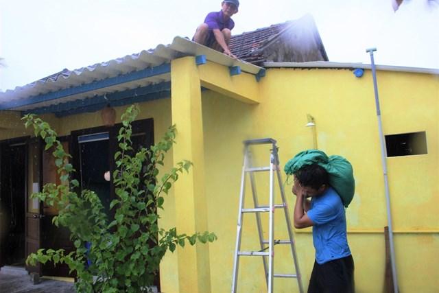Người dân vận chuyển bao cát để chằng chống mái nhà.