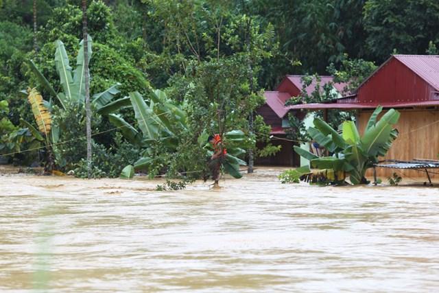 Lực lượng chức năng huyện Tây Giang cứu người ở thôn Ahu giữa dòng nước lũ.