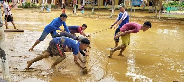 Thầy cô ở Trường phổ thông dân tộc bán trú THCS Nguyễn Bá Ngọc ở xã Bhlêê dọn bùn, đất.