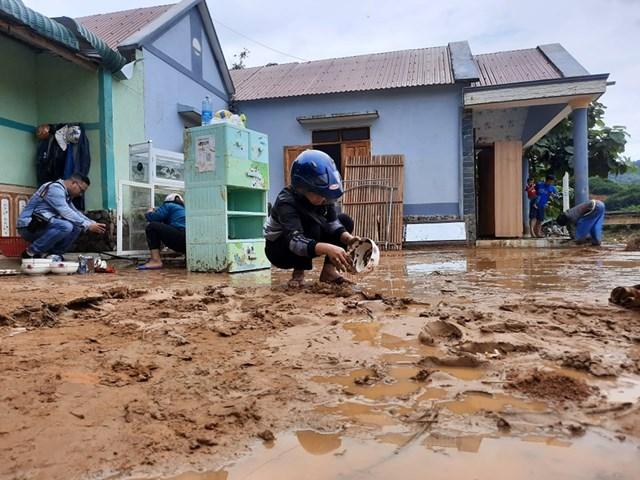 Người dân dọn dẹp bùn đất tại nhà sau lũ.