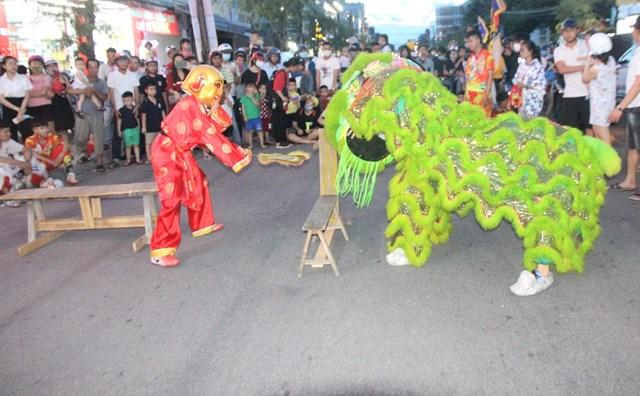 Rất đông người dân xem một đội lân đang biểu diễn.