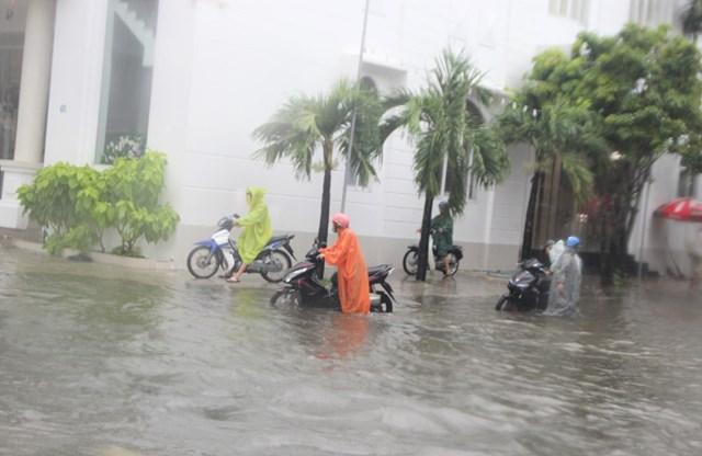 Người dân dặt bộ xe máy qua các đoạn đường ngập nước.