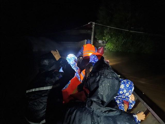 Giữa cơn mưa tầm tã, nước lũ dâng cao, chiếc thuyền nhôm đưa người đến nơi an toàn.