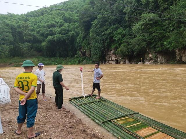 Cán bộ đồn biên phòng Na Mèo tham gia hỗ trợ người dân đối phó với mưa lũ.