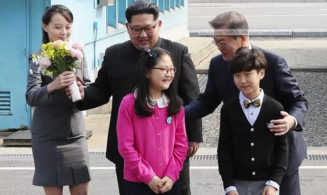 """Cố Chủ tịch Kim Jong-il thường gọi Kim Yo-jong là """"Yo-jong ngọt ngào và công chúa """". Ông rất tự hào về cô con gái út khi thấy cô bày tỏ sự quan tâm và năng khiếu về chính trị. Trong ảnh: Kim Yo-jong, em gái và cố vấn thân cận của nhà lãnh đạo Triều Tiên Kim Jong-un, mang theo một bó hoa khi ông và Tổng thống Hàn Quốc Moon Jae-in chụp ảnh với các em nhỏ sau khi gặp gỡ tại Đường phân giới quân sự giữa Triều Tiên và Hàn Quốc trước hội nghị thượng đỉnh của họ tại Panmunjom, ngày 27/4/2018."""