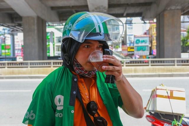 """Là xe ôm công nghệ ở Hà Nội, anh Hoàng Hùng Giang (35 tuổi) cũng cảm nhận được sự vất vả và khó khăn khi phải chở khách dưới thời tiết nắng nóng như này. """"Mình rất cám ơn những người đã lên ý tưởng này, góp phần giúp những người lao động như mình đỡ vất vả hơn. Cốc nước thực sự rất ngon."""", anh Giang chia sẻ."""