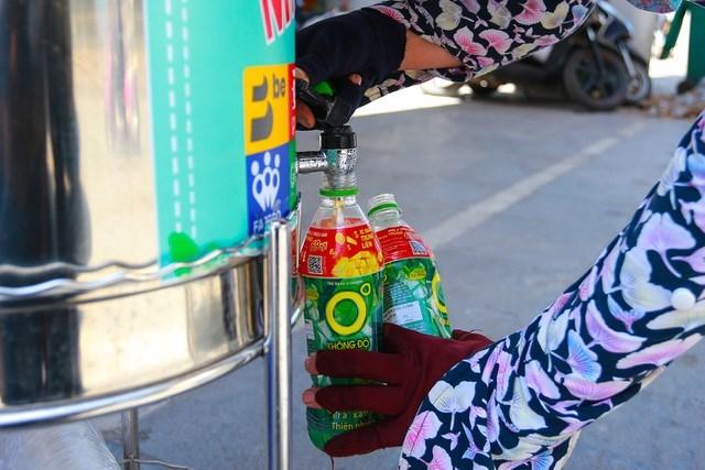 Mưu sinh với nghề bán bánh rán hơn chục năm nay, cô Nguyễn Thị Mai (Hà Nam), dù khá mệt mỏi nhưng dường như đã quá quen với cái nóng ở Thủ đô. Biết địa điểm này khá sớm nên cô thường xuyên qua đây để lấy nước. Cô Mai mang theo chai nhựa để uống riêng và lấy thêm cho buổi chiều.