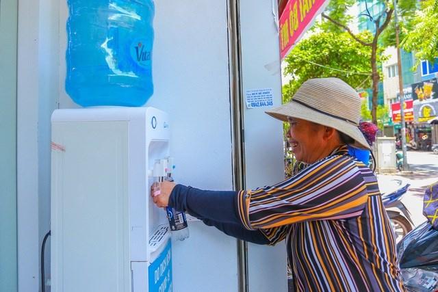Nụ cười trên khuôn mặt người phụ nữ đánh giầy khi đến với điểm cung cấp nước uống miễn phí.