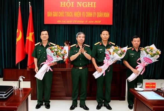 Thượng tướng Đỗ Căn trao quyết định và chúc mừng các cán bộ được bổ nhiệm chức vụ mới.