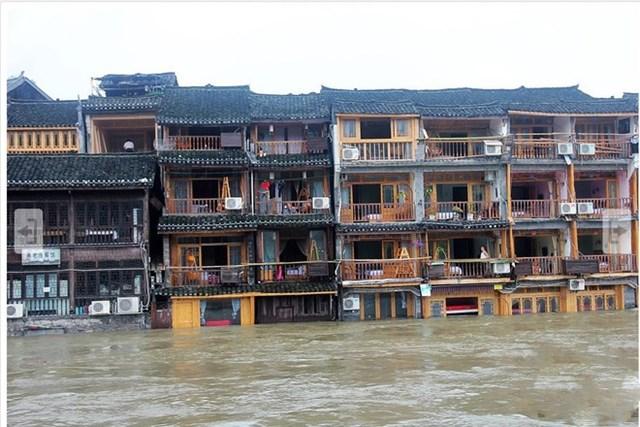 Ngày 27/6, nước dâng lũ dâng lên tới lầu 1 của hai dãy nhà dọc sông Đà Giang ở Phượng Hoàng cổ trấn. (Ảnh chụp màn hình China News).