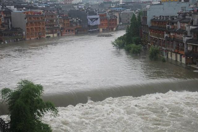 Kể từ tối 25.6, Phượng Hoàng trấn cổ hứng đợt mưa to, khiến nhiều nơi ngập nặng. Cầu nhảy đá trên sông Đà Giang bị nhấn chìm. (Ảnh chụp màn hình News.163.com).