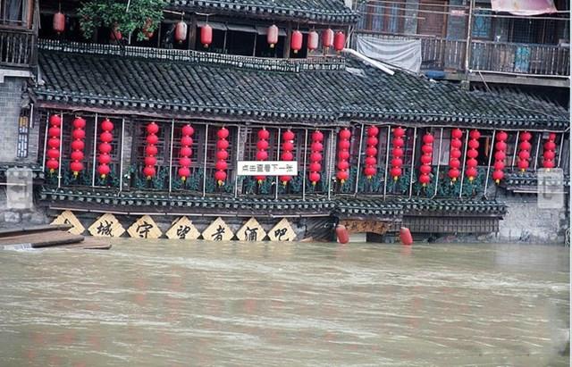 Cảnh nhiều ngôi nhà nằm hai bên bờ sông Đà Giang ở Phượng Hoàng cổ trấn chìm trong nước lũ hôm 27/6. (Ảnh chụp màn hình China News).