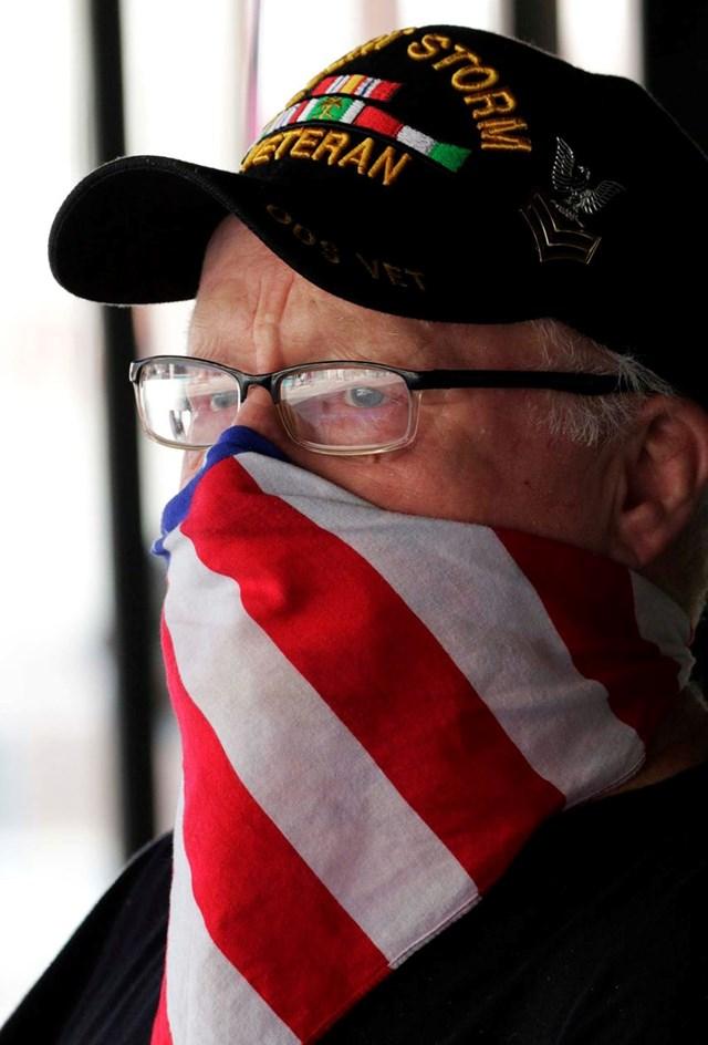 Một người dân Mỹ đeo khẩu trang trong khi theo dõi sự kiện diễu hành Ngày 4/7 diễn ra ở Manitowoc, bang Wisconsin.