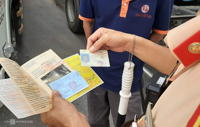 CSGT Bắc Ninh kiểm tra giấy tờ xe của tài xế ôtô trên Quốc lộ 17. Ảnh: Bá Đô.