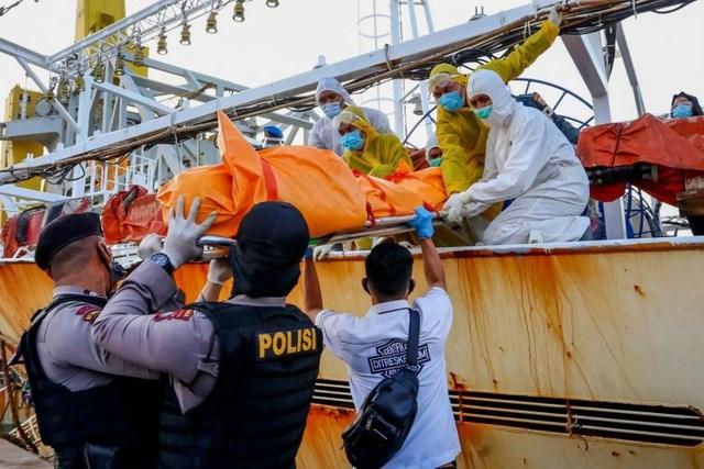 Thi thể thuyền viên Indonesia được đưa xuống khỏi tàu cá Trung Quốc (Ảnh: AFP).