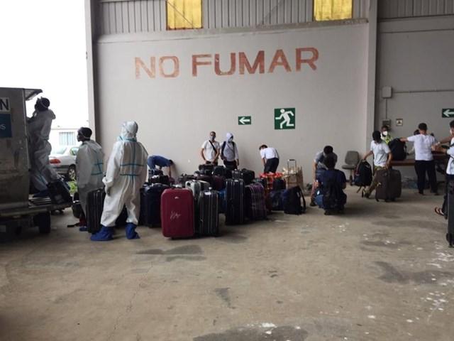 Đội hậu cần kỹ thuật trên máy bay đang chuẩn bị đồ đạc và đưa hành lý lên máy bay.
