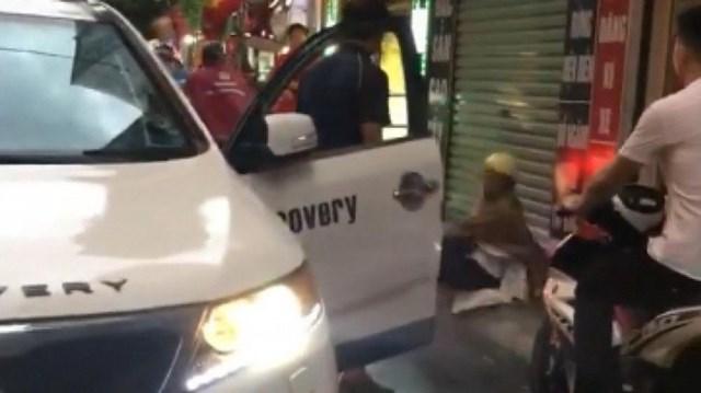 Hình ảnh cắt từ clip người đàn ông đi xe KIA Sorento BKS 30A - 684.13 thẳng tay tát một phụ nữ đi xe máy chở theo 2 con nhỏ trên đường ở Hà Nội.