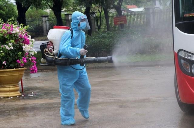 Nhân viên y tế khử trùng các phương tiện ra vào khu vực bệnh viện dã chiến. (Ảnh: Quốc Dũng/TTXVN).