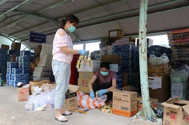 Các điều dưỡng của Trung tâm y tế huyện Hòa Vang có thêm nhiệm vụ phân chia đồ dùng, nhu yếu phẩm. (Ảnh: Quốc Dũng/TTXVN).