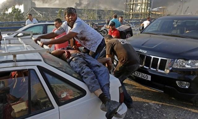 Người đàn ông bị thương nằm phía sau một chiếc ôtô trước khi được đưa khỏi hiện trường vụ nổ ở Beirut, Lebanon hôm 4/8. Ảnh: AFP.