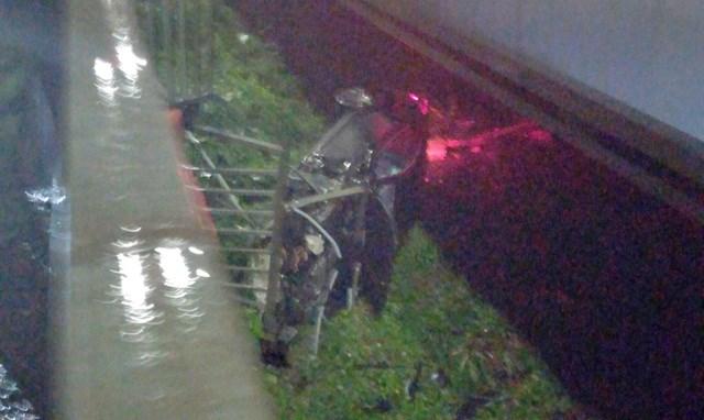 Porsche rơi xuống bãi đất trống dưới cầu Sài Gòn. (Ảnh: Huỳnh Phụng).