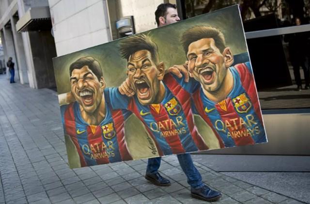 """Một người đàn ông mang theo bức tranh vẽ các chân sút của Barcelona: Luis Suarez , Neymar và Messi do họa sĩ biếm họa Tây Ban Nha Vizcarra vẽ tới buổi giới thiệu ấn bản thứ 12 của cuốn sách có tựa đề """"Relats solidaris de l 'esport"""" (Những câu chuyện về sự đoàn kết trong thể thao) tại Barcelona, ngày 17/2/2017."""