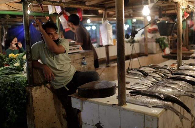 Các lệnh cấm và hạn chế ảnh hưởng đến nhiều lĩnh vực kinh doanh. Cả công ty lớn và công ty nhỏ đều bị thiệt hại. Trong ảnh là một người bán hàng đeo khẩu trang buồn bã đợi người mua tại một chợ cá ở Jakarta, Indonesia.