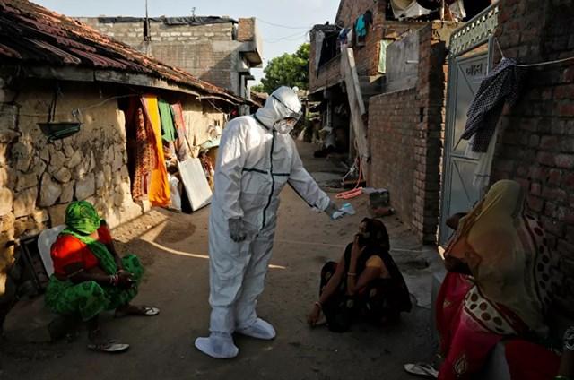Tốc độ lây lan của Covid-19 ở Ấn Độ đang gia tăng đến mức không lâu nữa quốc gia này có thể trở thành quốc gia đứng đầu thế giới về số lượng người nhiễm bệnh. Trong ảnh: Các nhân viên y tế kiểm tra thân nhiệt cho cư dân các khu vực nghèo của Ấn Độ.