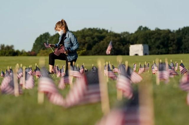 Một cô gái trẻ đeo khẩu trang đang cắm cờ Mỹ để tưởng nhớ những người thiệt mạng bởi Covid-19 tại Công viên National Mall ở Washington. Tại Mỹ, số người chết do Covid-19 đã vượt quá 200 nghìn người.