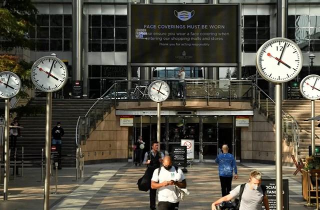 Trong khu thương mại Canary Wharf ở London, một màn hình lớn nhắc nhở về các quy tắc đeo mặt nạ. Số lượng người trên đường phố cũng giảm đáng kể.