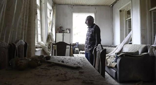 Một người dân địa phương đứng bên trong một căn phòng trong một tòa nhà bị hư hại ở Khodzhavend (Martuni) thuộc Cộng hòa tự xưng Nagorno-Karabakh sau khi bị pháo kích.