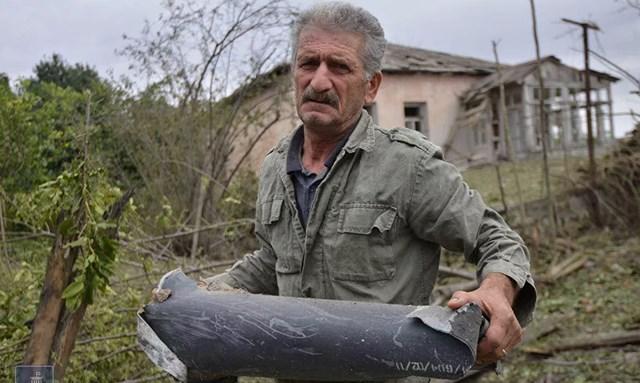 Người đàn ông cầm trên tay phần còn lại của một quả bom.