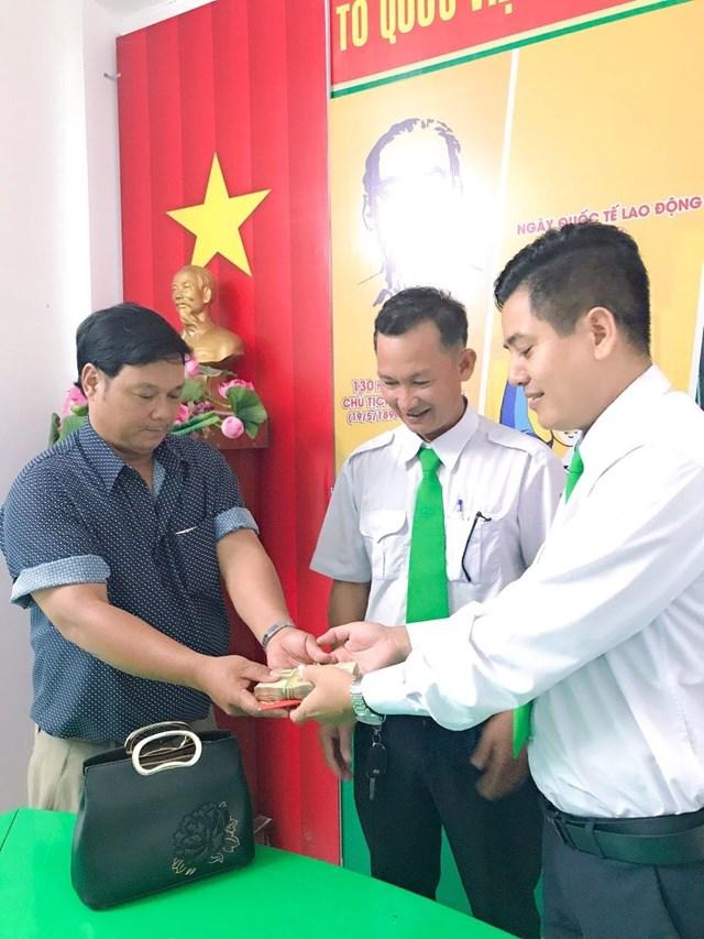 Đại diện taxi Mai Linh Đắk Lắk và tài xế Phạm Văn Sỹ (người ở giữa) trao lại số tài sản bị đánh rơi cho chủ nhân.