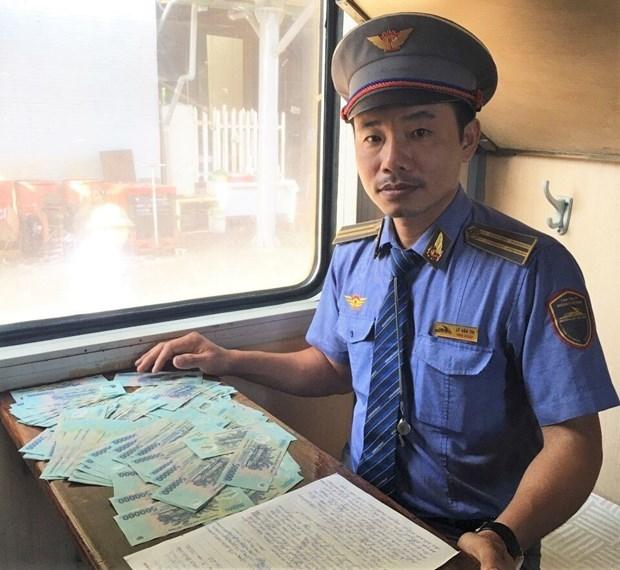Trưởng tàu lập biên bản hành khách bỏ quên 100 triệu trên tàu để bàn giao, trao trả hành khách. (Ảnh: VNR cung cấp). Nguồn: TTXVN.