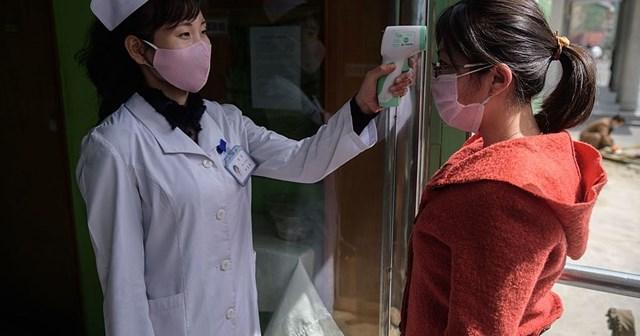 Nhân viên y tế Triều Tiên thực hiện kiểm tra thân nhiệt. Nguồn: Mirror.