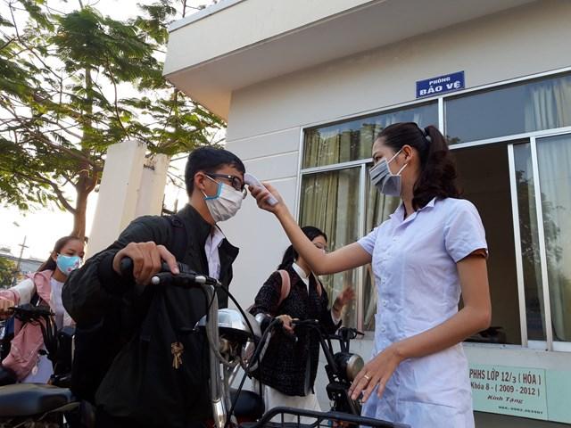 Đo thân nhiệt cho học sinh trước khi vào học.