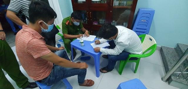 Phan Quang Hùng (áo trắng) làm việc với cơ quan chức năng. (Ảnh CTV).
