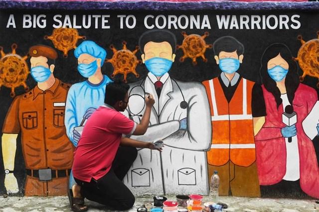 Một nghệ sĩ ở Kolkata, Ấn Độ vẽ tranh tôn vinh các y, bác sĩ ở tuyến đầu chống dịch Covid-19. (Nguồn: AFP).