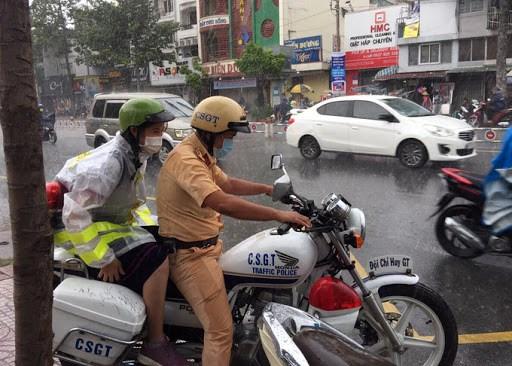Đại uý Nguyễn Anh Tú nhường áo mưa, chở nữ sinh đến điểm thi, ngày 9/8.