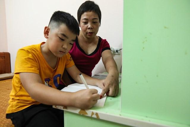 Chị Nguyễn Thị Thu Hoài dạy con ôn bài trước khi đến lớp.
