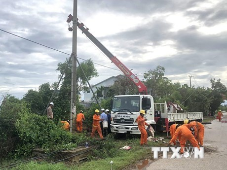 Công ty Điện lực Thừa Thiên-Huế khắc phục sự cố do mưa bão. (Ảnh: TTXVN phát).