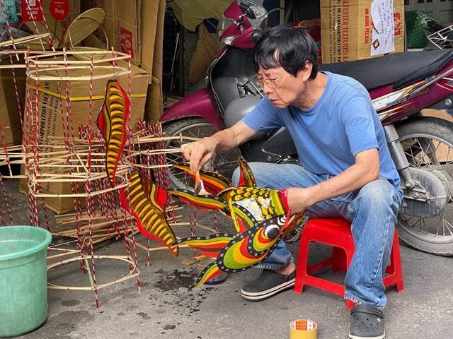 Nhà nghiên cứu Trịnh Bách khôi phục lại chiếc đèn Trung thu Cá cưỡi rồng. Ảnh: Thu Hòa.