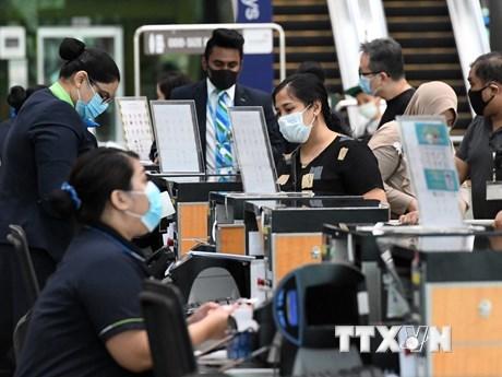 Hành khách làm thủ tục tại sân bay quốc tế Changi ở Singapore ngày 8/6/2020. (Ảnh: AFP/TTXVN).