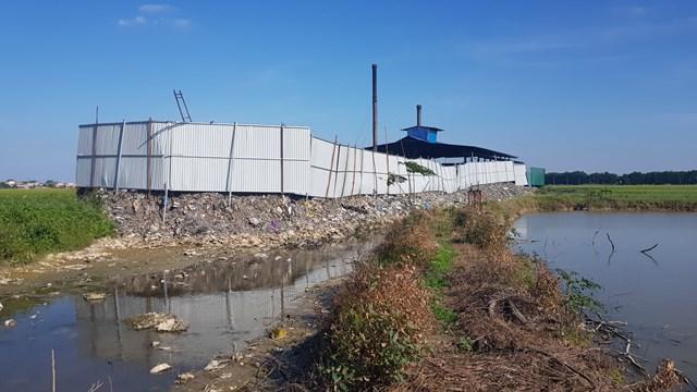 Phía sau của lò đốt rác, tro xỉ, nước rỉ rác đổ tràn xuống hệ thống kênh mương tưới tiêu.