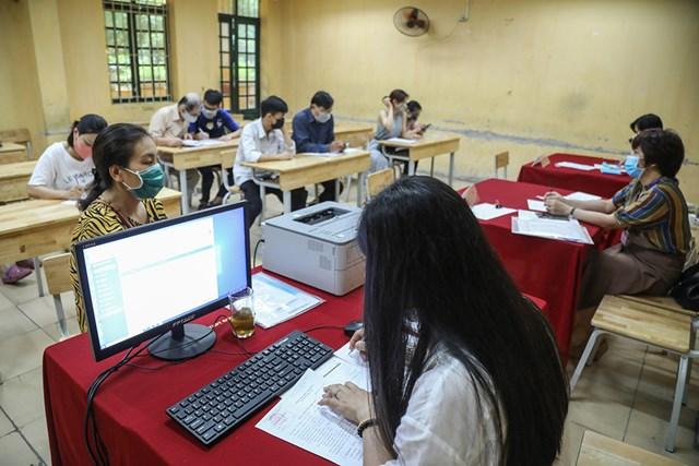Giáo viên nhà trường hỗ trợ phụ huynh học sinh làm thủ tục xác nhận nhập học cho con em của mình.