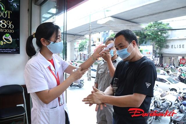 Người dân đến giao dịch tại cửa hàng được phát khẩu trang, rửa tay sát khuẩn và đo thân nhiệt.