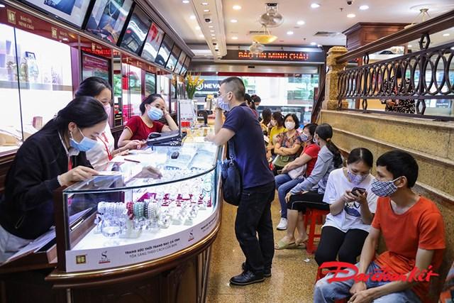 Người dân đến giao dịch đông và được nhân viên cửa hàng hướng dẫn ngồi khoảng cách nhất định, bắt buộc đeo khẩu trang nhằm đảm bảo an toàn phòng, chống dịch bệnh.