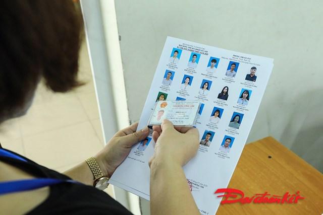 Cán bộ coi thi kiểm tra thẻ căn cước của thí sinh trước khi vào phòng thi.